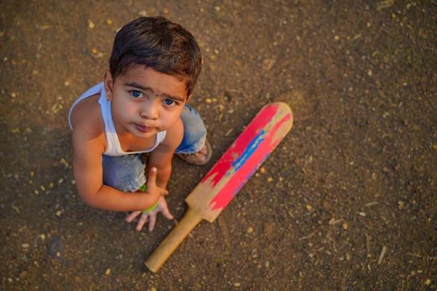 Kleines indisches kind, das cricket spielt