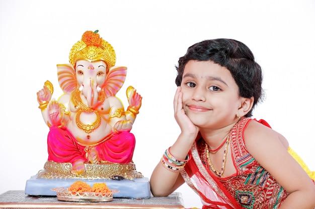 Kleines indisches mädchen mit lord ganesha und gebet, indisches ganesh-fest