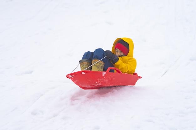 Kleines japanisches mädchen rutscht den schneeschlitten im skigebiet gala yuzawa hinunter