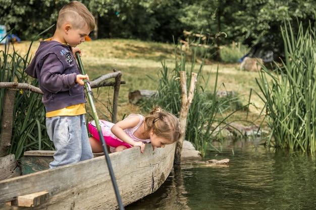 Kleines jungenmädchen, das in einem boot fischt