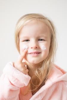 Kleines junges mädchen, das feuchtigkeitscreme auf ihrem gesicht aufträgt. hautpflege- und schönheitskonzept