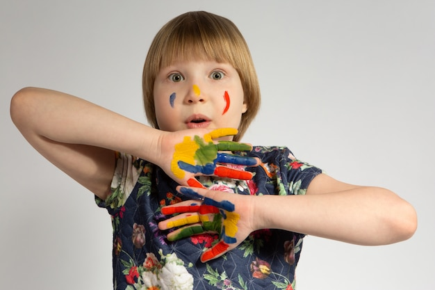 Kleines junges mädchen mit bunt bemalten händen und gesicht. lustiger gesichtsausdruck