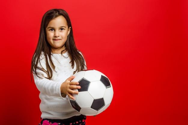 Kleines junges mädchen mit dem lächeln des fußballs in der hand lokalisiert auf rotem hintergrund