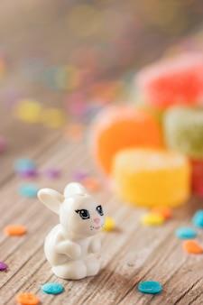 Kleines kaninchen auf bunten runden gummibonbons