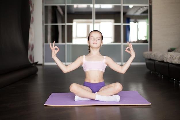 Kleines kaukasisches auf matte in der yogahaltung sitzendes und meditierendes mädchen.