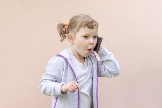 Kleines kaukasisches kindermädchen von fünf jahren, lockiges blondes mädchen mit einem telefon in ihren händen. das konzept der kindersucht nach geräten.