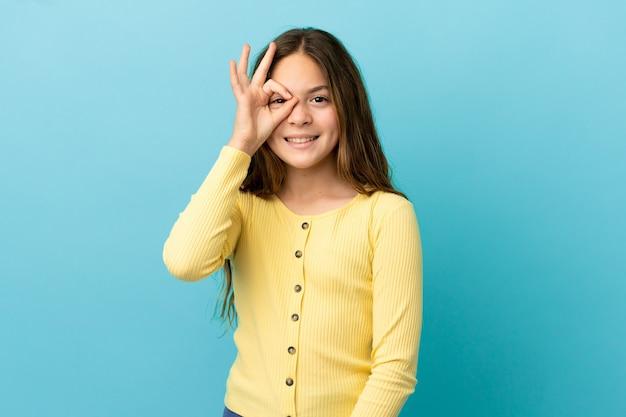 Kleines kaukasisches mädchen auf blauem hintergrund isoliert, das ein ok-zeichen mit den fingern zeigt