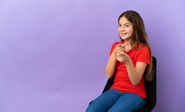 Kleines kaukasisches mädchen, das auf einem stuhl lokalisiert auf violettem hintergrund sitzt, überrascht und zeigt nach vorne