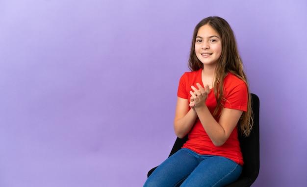 Kleines kaukasisches mädchen, das auf einem stuhl lokalisiert auf violettem hintergrund sitzt und applaudiert