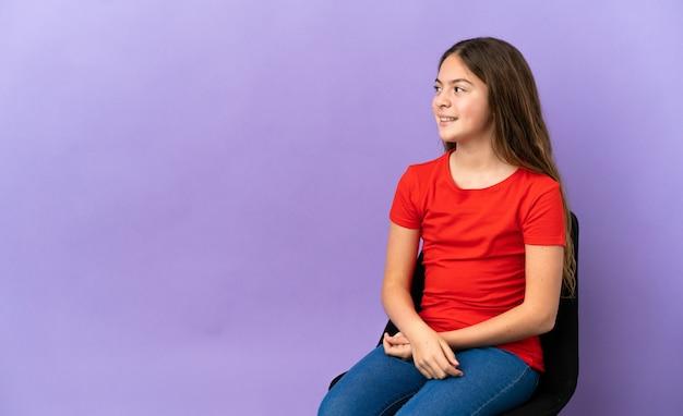 Kleines kaukasisches mädchen, das auf einem stuhl sitzt, der auf lila hintergrund isoliert ist, zur seite schaut und lächelt