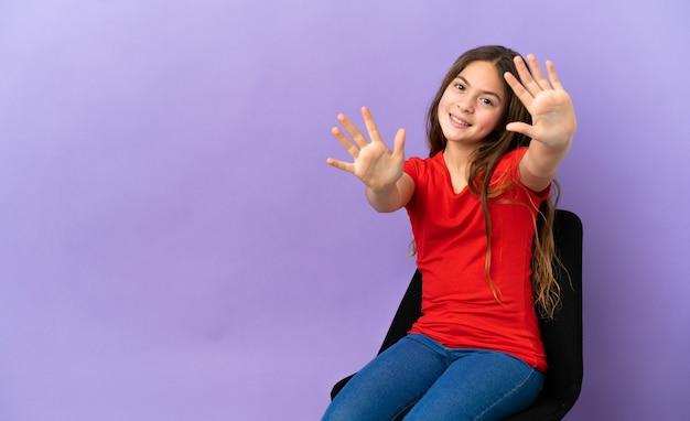 Kleines kaukasisches mädchen, das auf einem stuhl sitzt, der auf purpurrotem hintergrund isoliert ist und mit den fingern zehn zählt