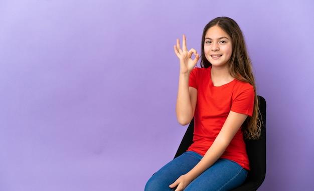 Kleines kaukasisches mädchen, das auf einem stuhl sitzt, der auf purpurrotem hintergrund lokalisiert wird, der okayzeichen mit den fingern zeigt