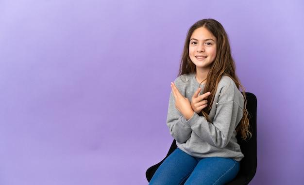 Kleines kaukasisches mädchen, das auf einem stuhl sitzt, der auf purpurrotem hintergrund lokalisiert wird, lächelt und zeigt victory-zeichen