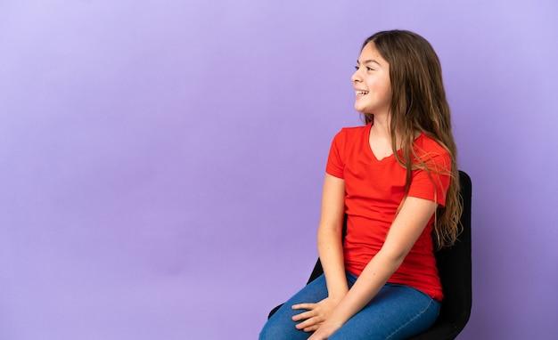 Kleines kaukasisches mädchen, das auf einem stuhl sitzt, der auf purpurrotem hintergrund lokalisiert wird und in seitlicher position lacht