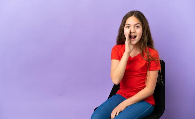 Kleines kaukasisches mädchen, das auf einem stuhl sitzt, der auf purpurrotem hintergrund lokalisiert wird und mit weit geöffnetem mund schreit