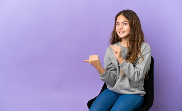 Kleines kaukasisches mädchen, das auf einem stuhl sitzt, der auf violettem hintergrund isoliert ist und auf die seite zeigt, um ein produkt zu präsentieren