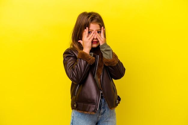 Kleines kaukasisches mädchen, das auf gelbem hintergrund isoliert ist, blinkt erschrocken und nervös durch die finger.