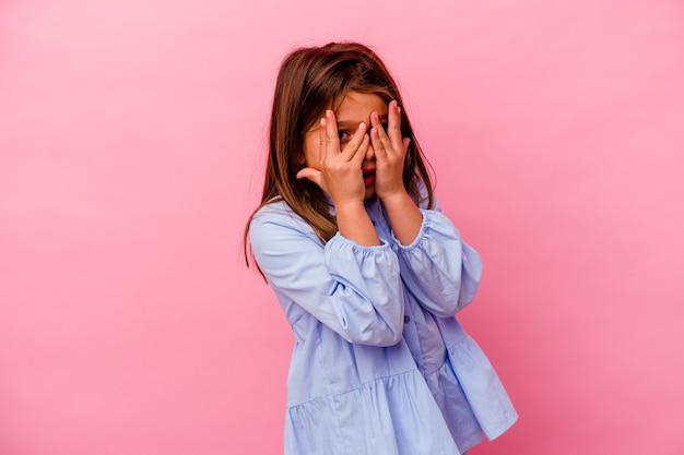 Kleines kaukasisches mädchen, das auf rosa blinzeln durch erschrockene und nervöse finger isoliert wird.