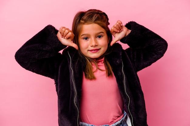 Kleines kaukasisches mädchen, das auf rosafarbenem hintergrund isoliert ist, fühlt sich stolz und selbstbewusst, beispiel zu folgen.