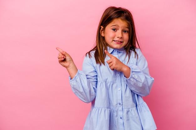 Kleines kaukasisches mädchen, das auf rosafarbenem hintergrund isoliert ist, schockiert und zeigt mit dem zeigefinger auf einen kopierraum.