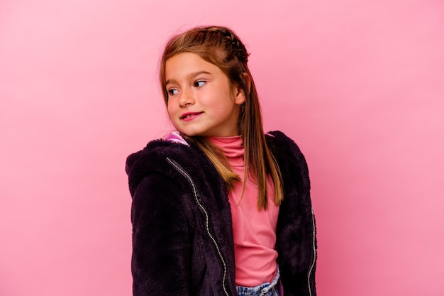 Kleines kaukasisches mädchen, das auf rosafarbenem hintergrund isoliert ist, sieht beiseite lächelnd, fröhlich und angenehm aus.