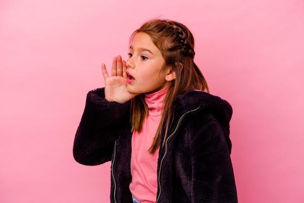 Kleines kaukasisches mädchen, das auf rosafarbenem hintergrund isoliert ist und die handfläche in der nähe des geöffneten mundes schreit und hält.