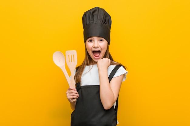 Kleines kaukasisches mädchen, das ein chefkostüm zujubelt sorglos und aufgeregt trägt. sieg-konzept.