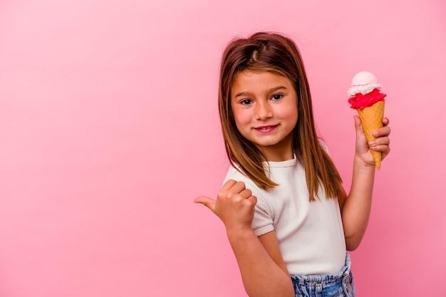 Kleines kaukasisches mädchen, das eis einzeln auf rosafarbenem hintergrund hält, zeigt mit dem daumenfinger weg, lacht und sorglos.