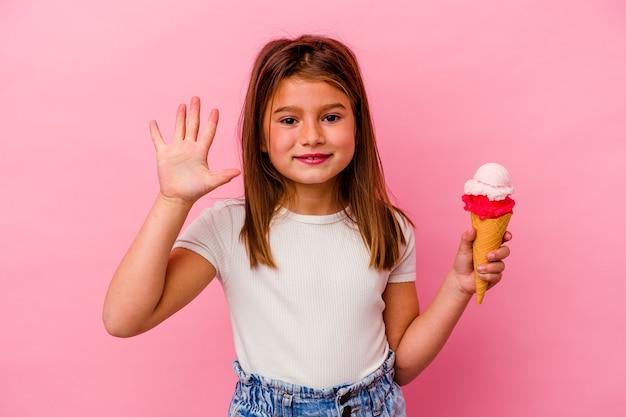 Kleines kaukasisches mädchen, das eis isoliert auf rosafarbenem hintergrund hält und fröhlich lächelt und nummer fünf mit den fingern zeigt.