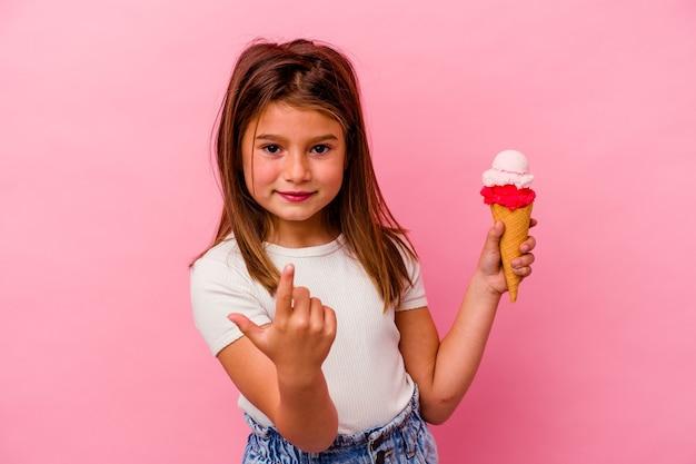 Kleines kaukasisches mädchen, das eiscreme lokalisiert auf rosa wand zeigt, die mit dem finger auf sie zeigt, als ob die einladung näher kommt.