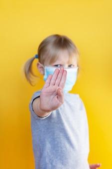 Kleines kaukasisches mädchen, das maske gegen coronavirus covid-19 trägt