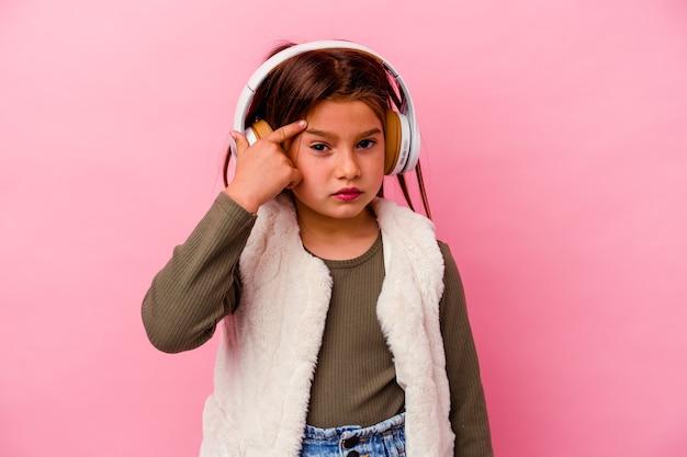 Kleines kaukasisches mädchen, das musik einzeln auf rosafarbenem hintergrund hört und eine enttäuschungsgeste mit dem zeigefinger zeigt.