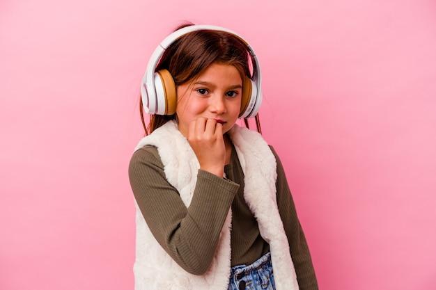 Kleines kaukasisches mädchen, das musik einzeln auf rosafarbenem hintergrund hört und fingernägel beißt, nervös und sehr ängstlich.