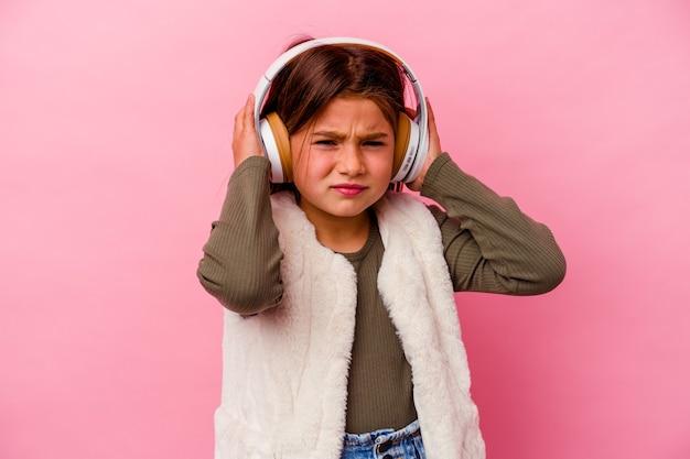 Kleines kaukasisches mädchen, das musik hört, die auf rosa bedeckenden ohren mit händen lokalisiert wird.