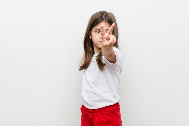 Kleines kaukasisches mädchen, das nummer zwei mit den fingern zeigt.