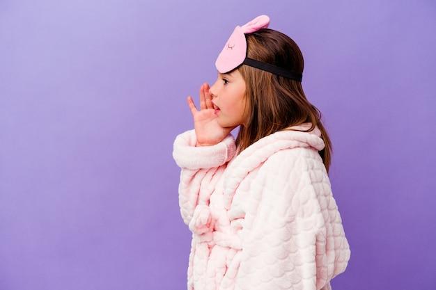 Kleines kaukasisches mädchen, das pyjama trägt, isoliert auf violettem hintergrund, schreit und hält palme in der nähe des geöffneten mundes