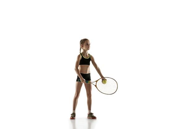 Kleines kaukasisches mädchen, das tennis lokalisiert auf weißer wand spielt