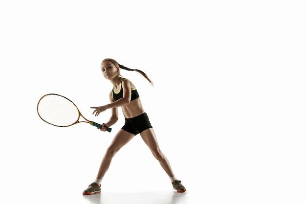 Kleines kaukasisches mädchen, das tennis spielt, lokalisiert auf weißer wand