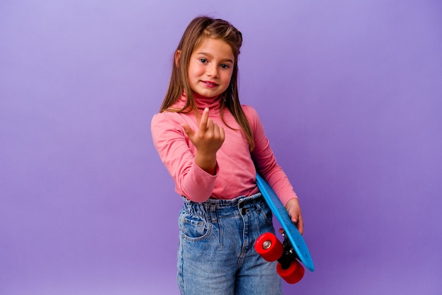 Kleines kaukasisches mädchen des skaters lokalisiert auf der blauen wand, die mit dem finger auf sie zeigt, als ob die einladung näher kommt.