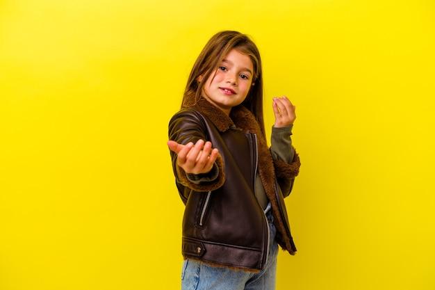 Kleines kaukasisches mädchen einzeln auf gelbem hintergrund, das mit dem finger auf sie zeigt, als ob es einladend wäre, näher zu kommen.