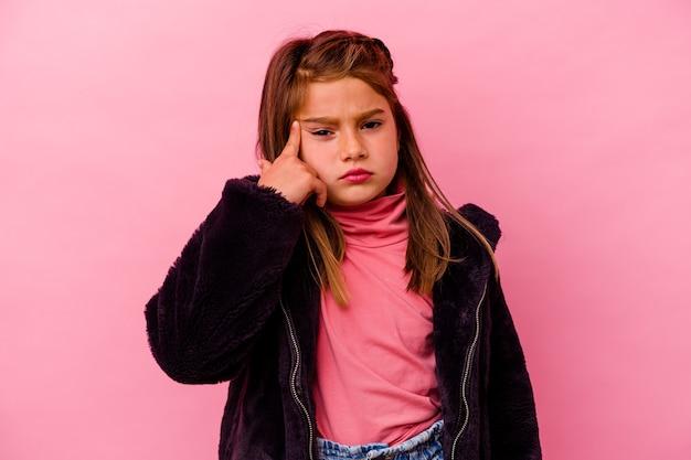 Kleines kaukasisches mädchen einzeln auf rosafarbenem hintergrund, das eine enttäuschungsgeste mit dem zeigefinger zeigt.
