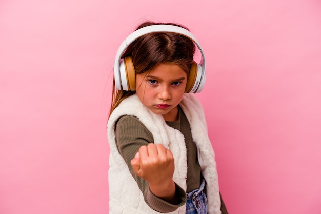 Kleines kaukasisches mädchen hört musik einzeln auf rosafarbenem hintergrund, die faust zur kamera zeigt, aggressiver gesichtsausdruck.