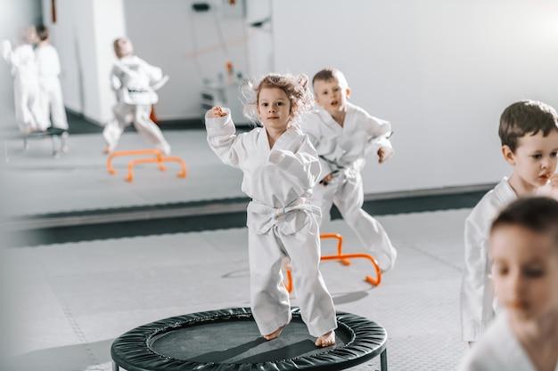 Kleines kaukasisches mädchen im dobok, das auf trampolin springt und sich für taekwondo-training aufwärmt.