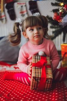 Kleines kaukasisches mädchen in der rosa strickjacke mit einem geschenk in ihren händen, die zu hause unter einem baum des neuen jahres sitzen