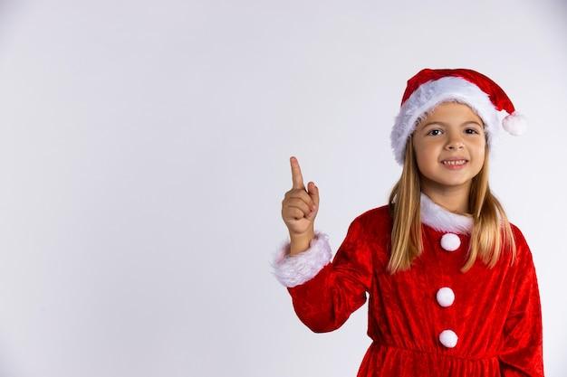 Kleines kaukasisches mädchen in der weihnachtsmannmütze und im roten kostüm mit dem schönen lächeln zeigt den finger. isoliert