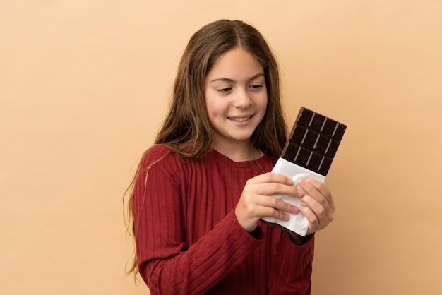 Kleines kaukasisches mädchen isoliert auf beigefarbenem hintergrund, das eine schokoladentablette nimmt und glücklich ist