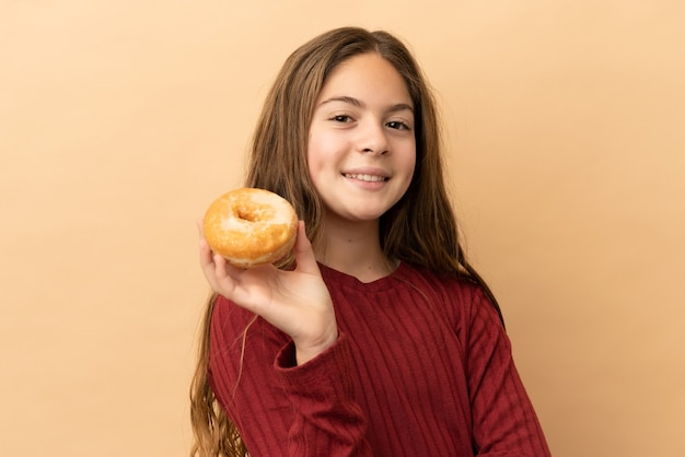 Kleines kaukasisches mädchen isoliert auf beigefarbenem hintergrund, das einen donut hält und glücklich