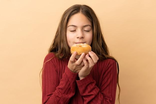 Kleines kaukasisches mädchen isoliert auf beigefarbenem hintergrund, das einen donut hält