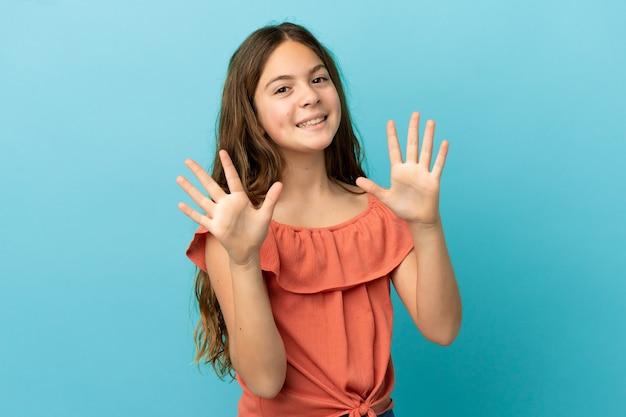 Kleines kaukasisches mädchen isoliert auf blauem hintergrund, das mit den fingern zehn zählt