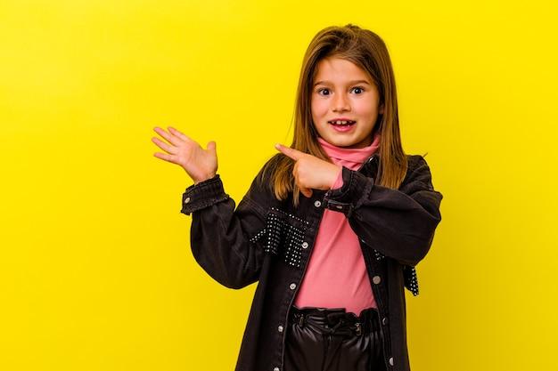 Kleines kaukasisches mädchen isoliert auf gelbem hintergrund lächelnd fröhlich mit nummer fünf mit den fingern.
